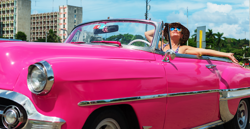 Smiling woman in classic car in Cuba