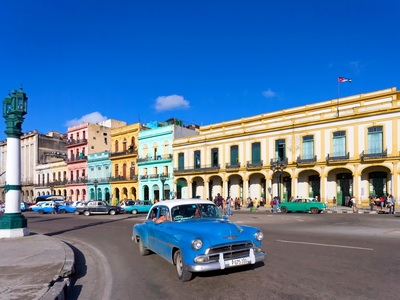 A vintage car drives through the colorful streets of Old Havana, Cuba